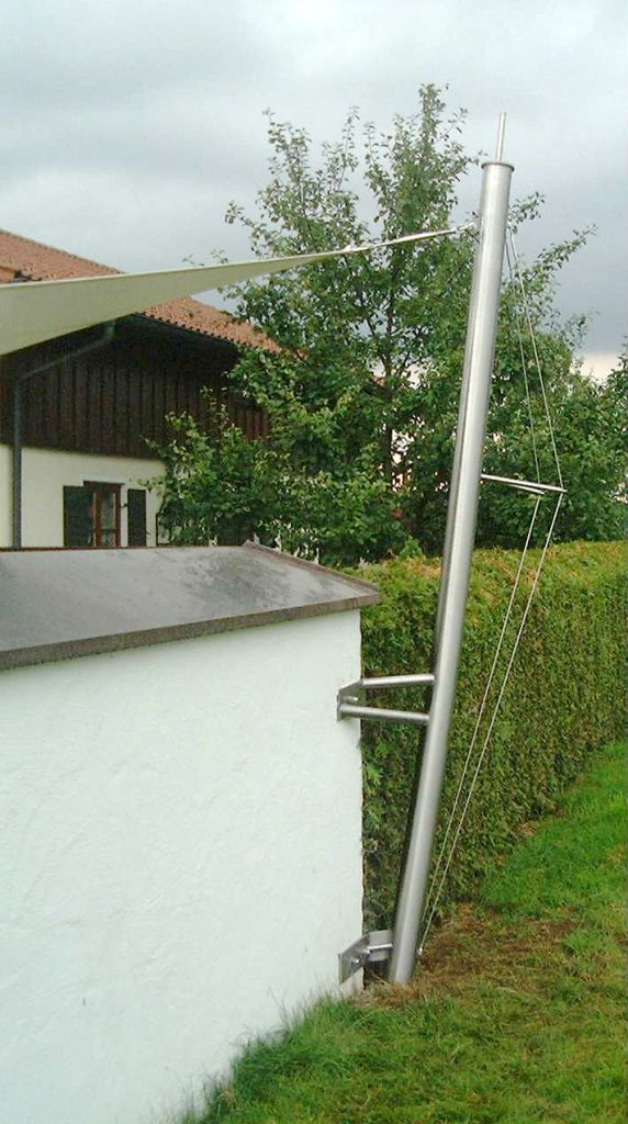 aeronautec Sonnensegelkonzept- jedes Sonnensegel wird nach Maß geplant und gefertigt. Edelstahlmastbefestigung an Gartenmauer